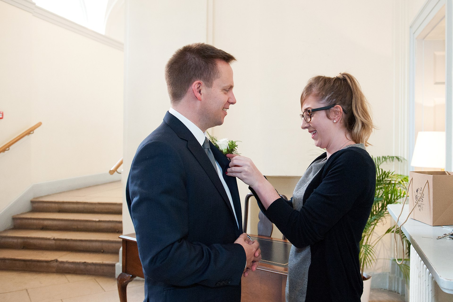 Chloe Gorham from Bovingdons Caterers fixes teh groom's buttonhole before his civil wedding ceremony