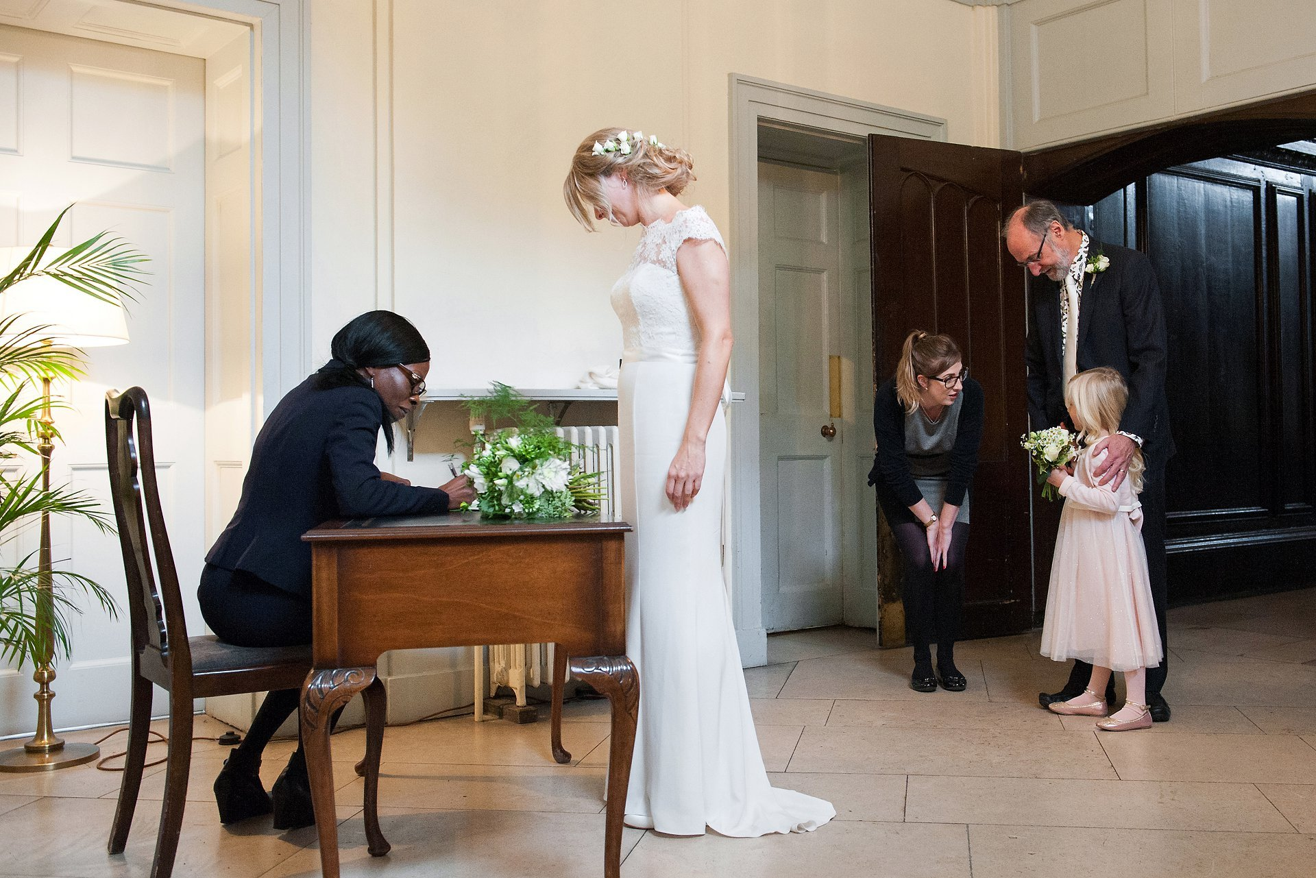 The bride completes the marriage certificate with a Registrar from Hammersmith & Fulham Register Office withe her father and daughter in the background