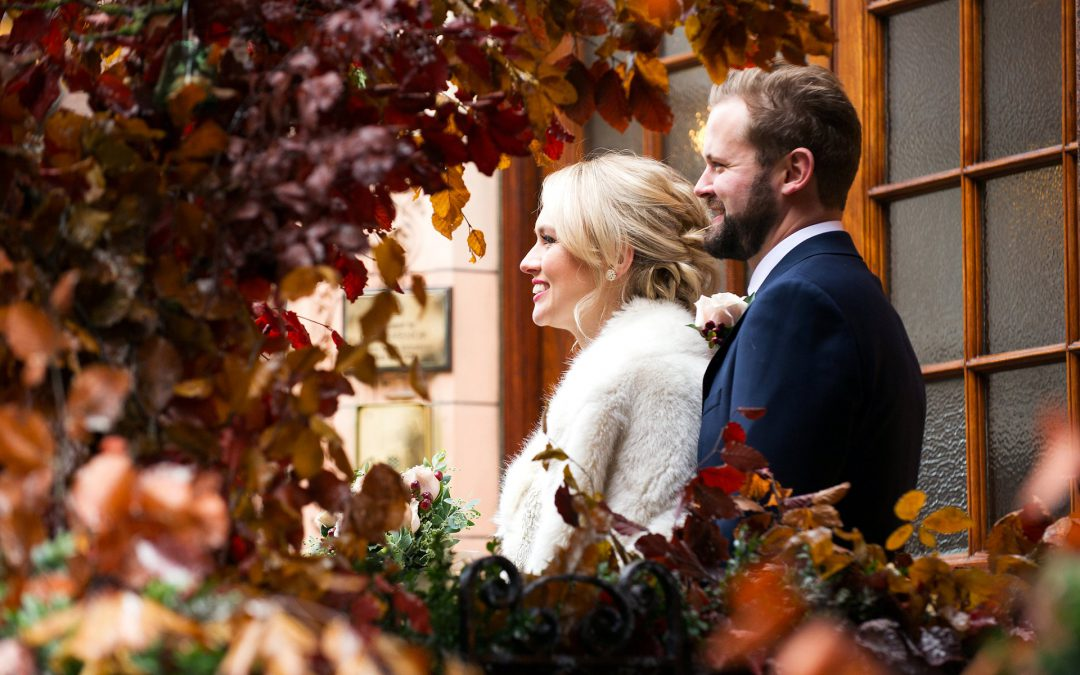 the red brick buildings and autumnal trees of mayfair frame this bride and groom on mount street