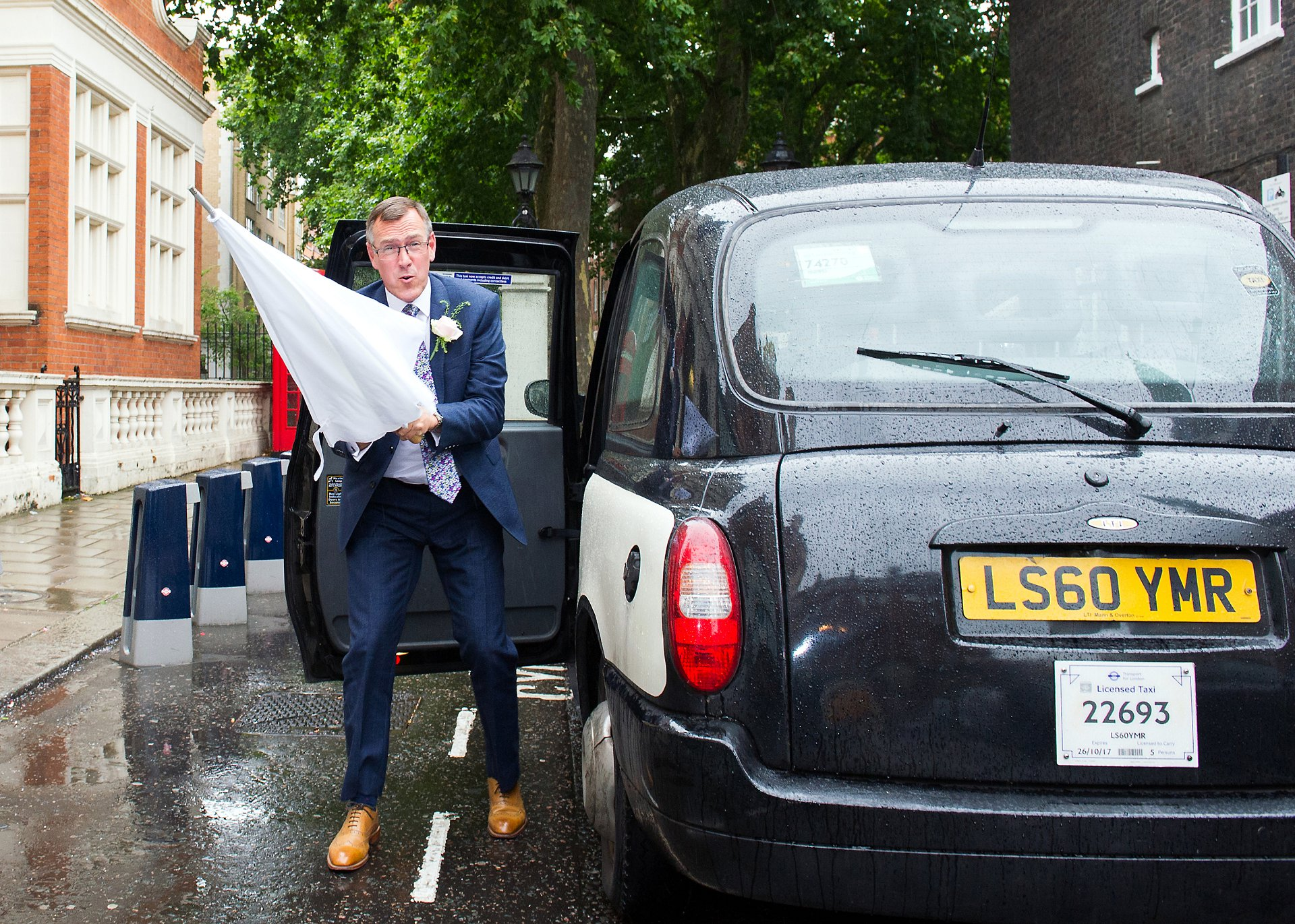 london black cab wedding photographer a groom exits with umbrella in mayfair