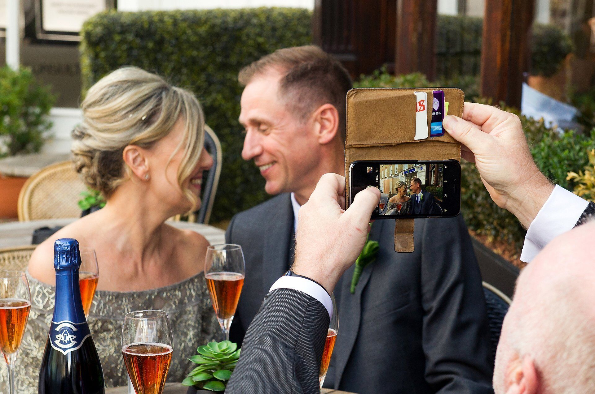 a guest takes a photo of bride and groom brenda and michael outside the harcourt in marylebone