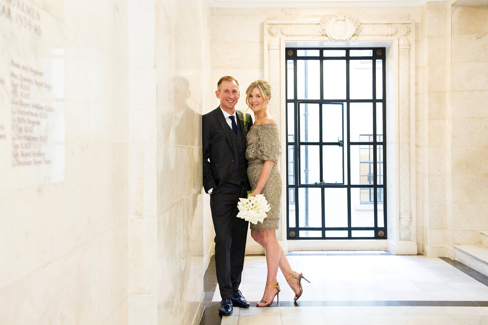 a stylish bride and groom pose on the mezzanine level by marylebone registry office wedding photographer emma duggan