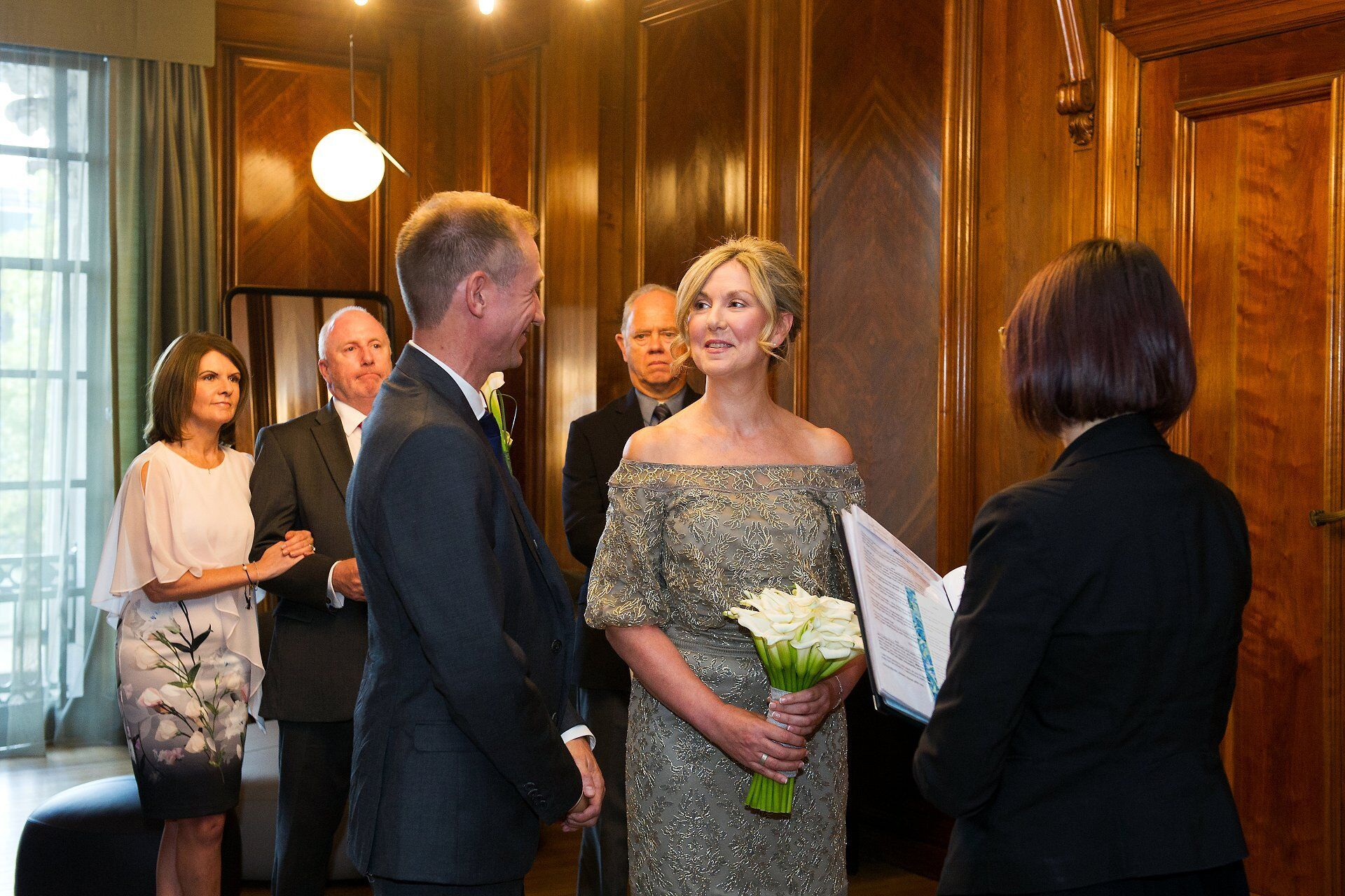 brenda and michael are watched by their three guests in the paddington room during their civil wedding ceremony