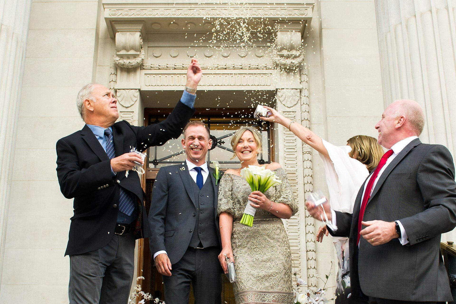 brenda and michael leave old marylebone town hall under a hail of confetti thrown by their three guests