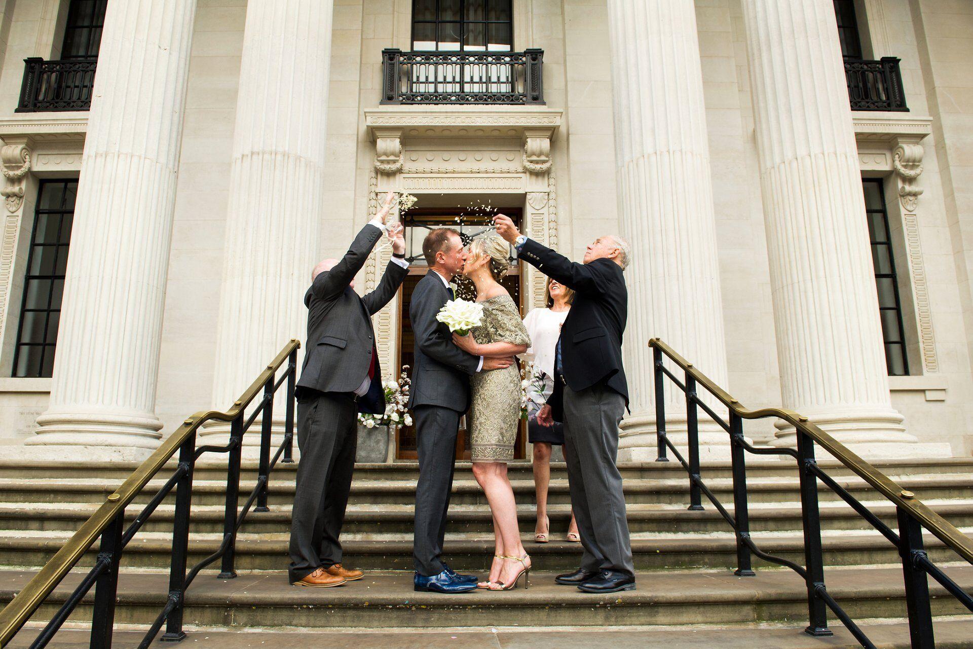 michael and brenda kissing on the steps of marylebone registry office with guests throwing confetti
