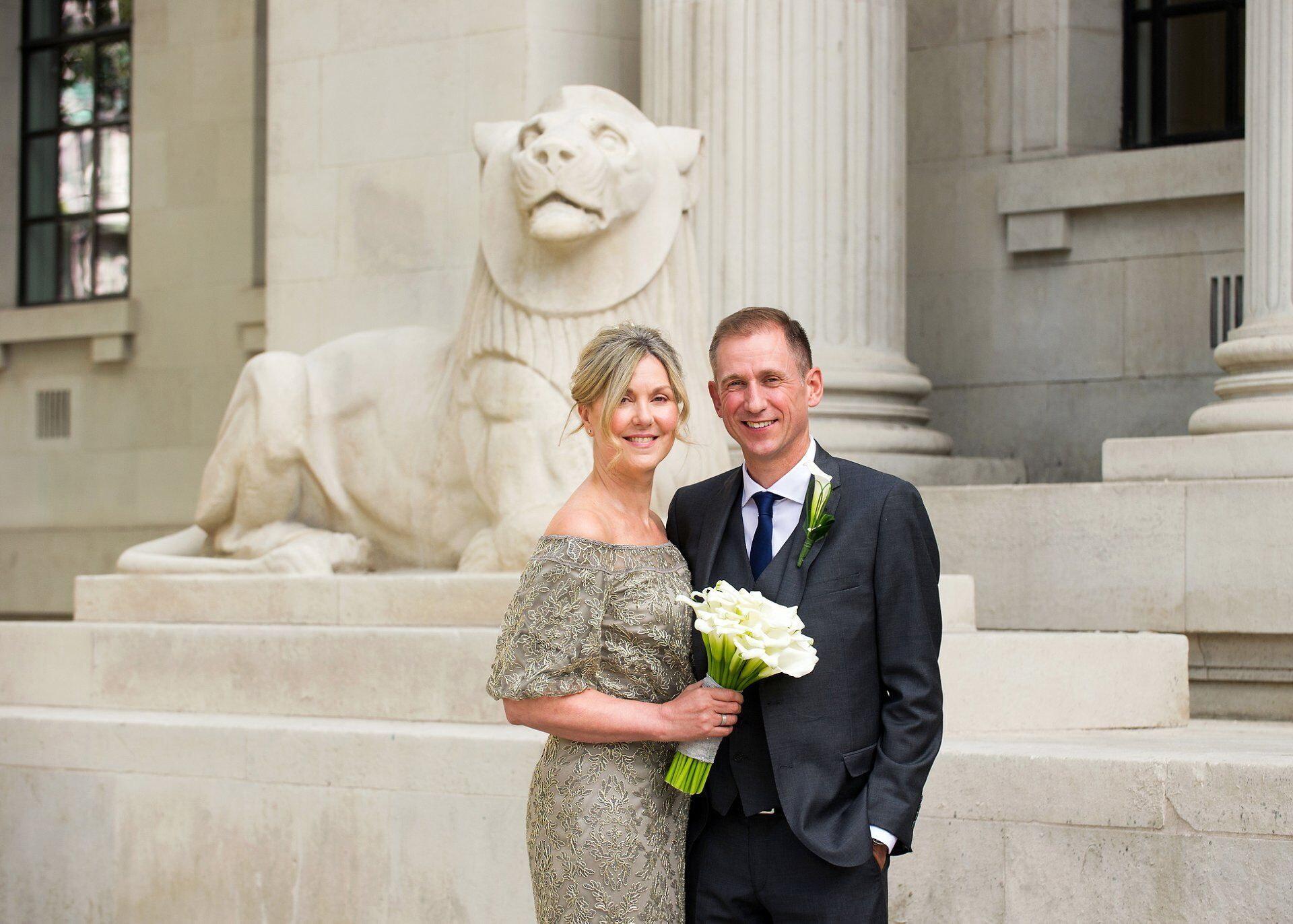 old marylebone town hall wedding photographer captures brenda and michael in front of a stone lion at old marylebone town hall