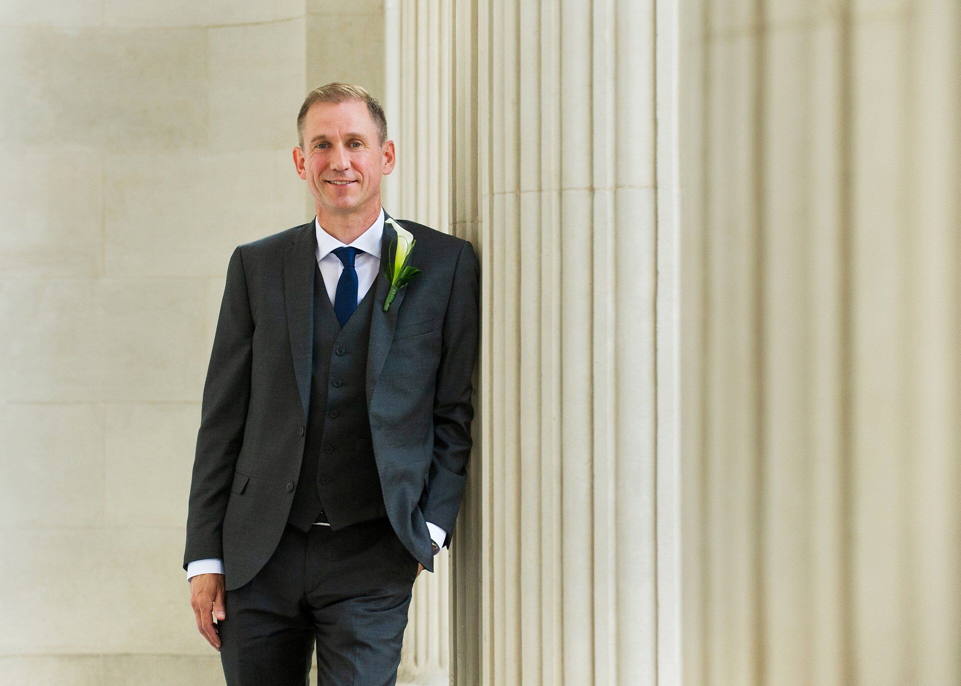 stylish groom in three piece dark grey suit leans against a fluted column at westminster council house with his hand in his pocket