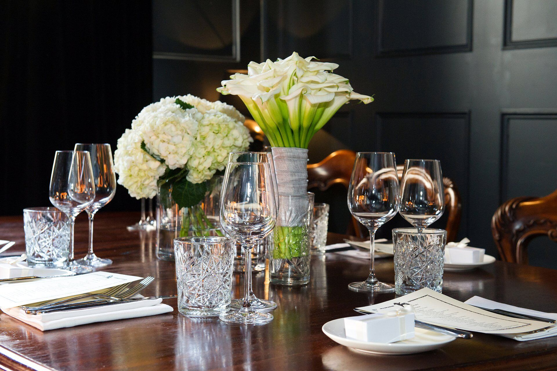 the black room at the harcourt in marylebone laid for a wedding and a party of five with the bride's calla lilies and a hydrangea centrepiece