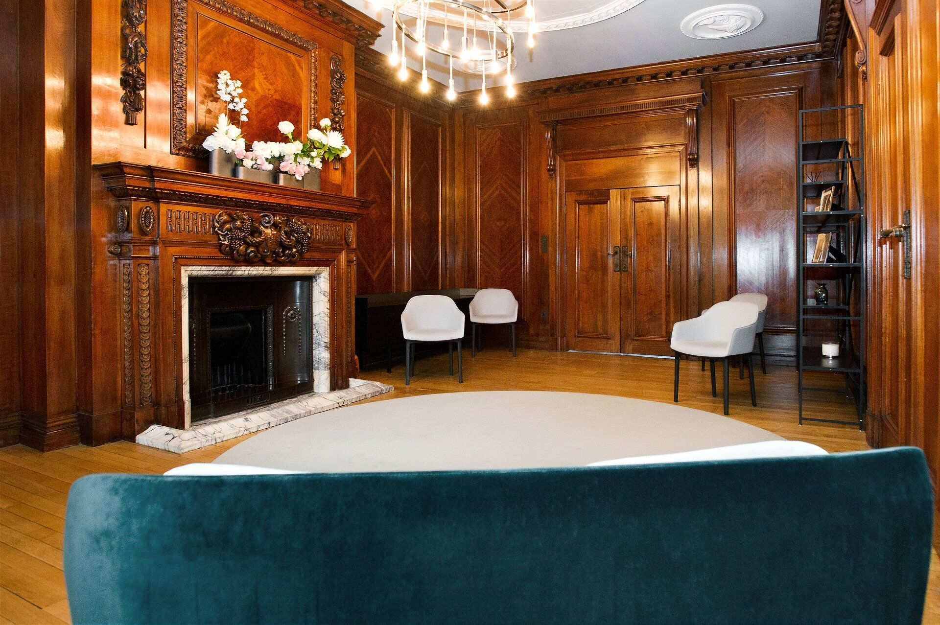 seating for 5 or 6 guests in the marylebone room with the couple stood in front of the fireplace