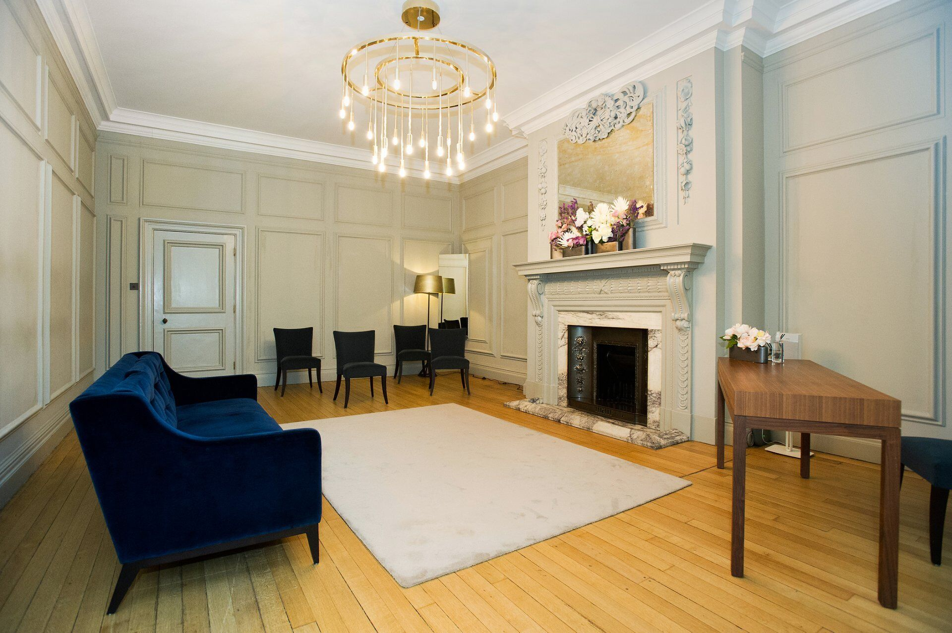 the soho room shows seating for 5 to 6 guests with the couple stood in front of the fireplace