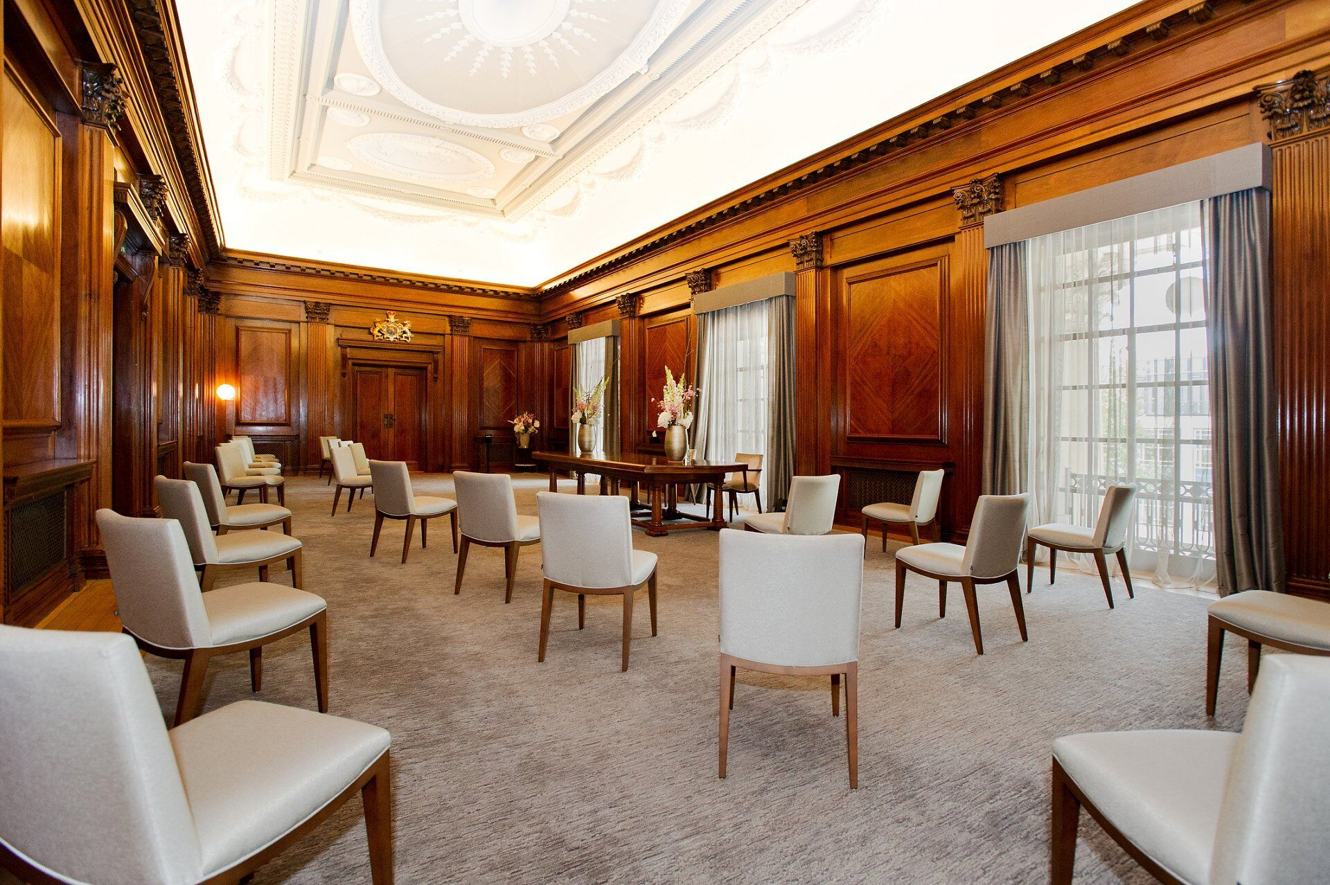 the westminster room now seats 26 guests with the couple standing in front of the grand table under new register office wedding guidelines - old marylebone town hall new ceremony room layouts
